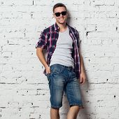foto of macho man  - Handsome stylish young man in jeans shorts and shirt - JPG
