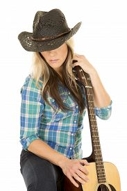 picture of cowgirls  - A cowgirl in her western hat looking down holding on to her guitar - JPG