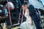 pic of locomotive  - Portrait of happy wedding couple near the old steam locomotive - JPG