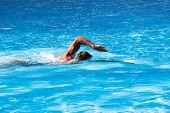 stock photo of crawl  - young man swim crawl style in outdoor swimming pool - JPG