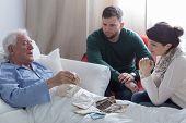 image of sick  - Older sick man in hospital opening old letters  - JPG