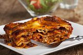 image of lasagna  - homemade lasagna on rustic wood with a fork - JPG
