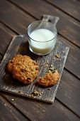 image of baked raisin cookies  - oatmeal cookies with raisins and a glass of milk on a dark surface  - JPG