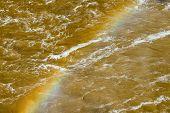 picture of breaker  - Vivid rainbow diagonally across churning muddy brown river water waves and breakers - JPG