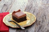 picture of chocolate fudge  - Chocolate sheet cake covered with chocolate icing on a plate with a fork - JPG