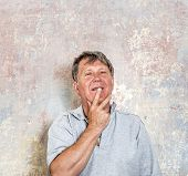 stock photo of rotten  - portrait of senior man in front of grungy old wall in a rotten house - JPG