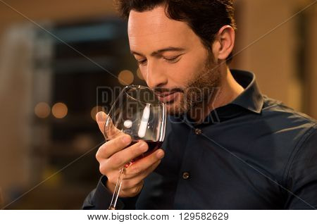 Handsome young man smelling red wine before drinking it. Young man drinking red wine in a luxury res