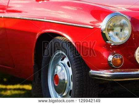 poster of Red vintage car. Close-up fragment of the red vintage car. Headlight of vintage red car. Retro car. Selective focus.