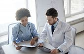 health care, people, technology and medicine concept - doctor and nurse with tablet pc computer and  poster