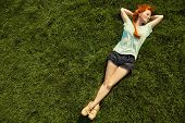 Relaxing Redhead Girl Lying On The Grass. Woman Relaxation Outdoor poster