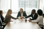 African Businessman And Caucasian Businesswoman Shaking Hands Over Conference Table At Multiracial G poster