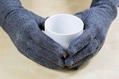 Empty White Mug With Gloves. Hands In Warm Gloves Holding A China Mug On A Wooden Kitchen Table. poster