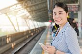 Girl Holding A Mobile Phone Standing On Platform poster