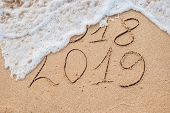 New Year 2019 Is Coming Concept - Inscription 2018 And 2019 On A Beach Sand, The Wave Is Almost Cove poster