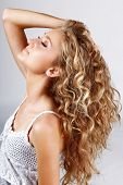 stock photo of strawberry blonde  - Beautiful strawberry blond teenage girl with long curly hair over grey studio background  - JPG