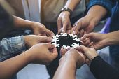 Closeup Image Of Many People Hands Holding A Jigsaw Puzzle In Circle Together poster