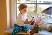 Happy Adorable Cute Baby Girl Sitting Near Window And Looking Outside On Snow On Winter Or Spring Da poster