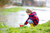Happy Little Kid Boy In Yellow Rain Boots Playing With Paper Ship Boat By Huge Puddle On Spring Or A poster