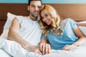 View Of Affectionate Couple Holding Hands In Bed poster