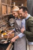 Husband Hugging Wife While She Cooking At Kitchen poster