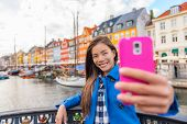 Selfie tourist girl taking photo with phone at Copenhagen Nyhavn, famous Europe tourism attraction.  poster