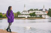 Woman in purple trench coat walking in city park relaxing on weekend. Person enjoying lake view in C poster