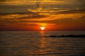 stock photo of promontory  - Dramatic red skies sunset over the sea horizon - JPG