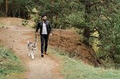 Contemporary young man in casualwear walking down footpath while holding leash of his purebred dog poster