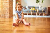 Beautiful toddler child girl wearing blue denim shirt sitting on the floor  poster