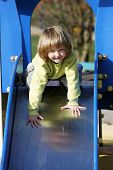 stock photo of toboggan  - Small child playing on colorful toboggan in autumn - JPG