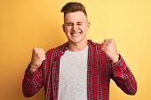 Young handsome man wearing casual shirt standing over isolated yellow background very happy and exci poster