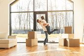 Young Couple Moves To A New Home. The Family Carries Boxes Of Things After Buying A Home. poster