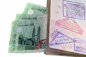 stock photo of ringgit  - An entry and exit immigration stamp in the passport upon entering Malaysia with Malaysian Ringgit - JPG