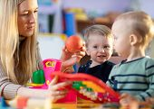 Children Toddlers And Nursery Teacher Play With Toy Scales In Kindergarten Playroom poster