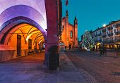 View of illuminated buildings and Christmas tree on cobblestone town square in evening in small town poster