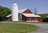 picture of silos  - Red barn and a silo by a gravel road - JPG
