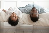 Smiling Black Dad And Toddler Son Lying Upside Down poster