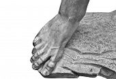 Foot. Fragment of an antique marble statue. Cracked ground in the background. Plaster limb, foot mal poster