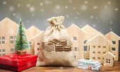 Money Bag, Wooden Houses, Christmas Tree And Gifts. Christmas Sale Of Real Estate. New Year Discount poster