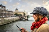 Woman Looking At Cell Phone. Woman Looking At Cell Phone While Walking In Paris. Woman Reading Messa poster