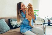 Playing With Cat At Home. Young Woman Sitting On Couch Teasing And Hugging Pet. poster