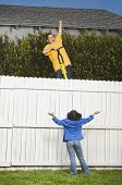 image of peeping tom  - Mixed Race boy trying to jump fence with pogo stick - JPG
