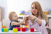 Baby Play With Babysitter Or Mom In Nursery Or Kindergarten poster