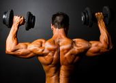 stock photo of bodybuilder  - rear view of bodybuilder training with dumbbells on black background - JPG