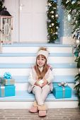 Merry Christmas, Happy Holidays! New Year 2020. Little Girl Sits With Gifts On Porch Of A House Deco poster