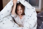 Closeup Portrait Of Happy Little Girl Sitting On Bed Under Blanket And Posing In Room Of Her Flat Ho poster