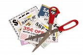 stock photo of coupon  - Horizontal shot of many coupons with a pair of red handled scissors - JPG