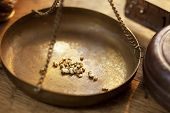 stock photo of gold nugget  - Weighing a gold nugget on a old brass scale dish for trade or exchange - JPG