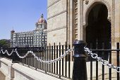stock photo of cameos  - Landscape of the Gateway of India its black and silver painted railings with a cameo view of the Taj Hotel with an angled view of an archway - JPG