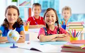 stock photo of preschool  - Portrait of two diligent girls looking at camera at workplace with schoolboys on background - JPG